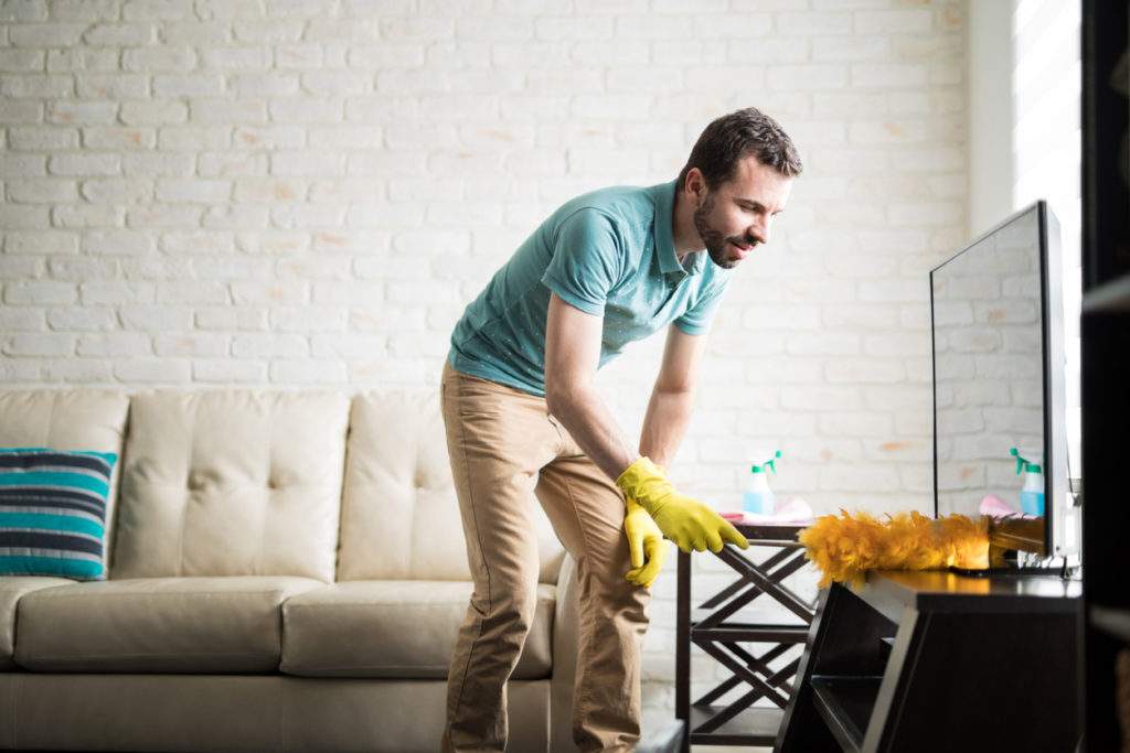 Young man cleaning with a duster