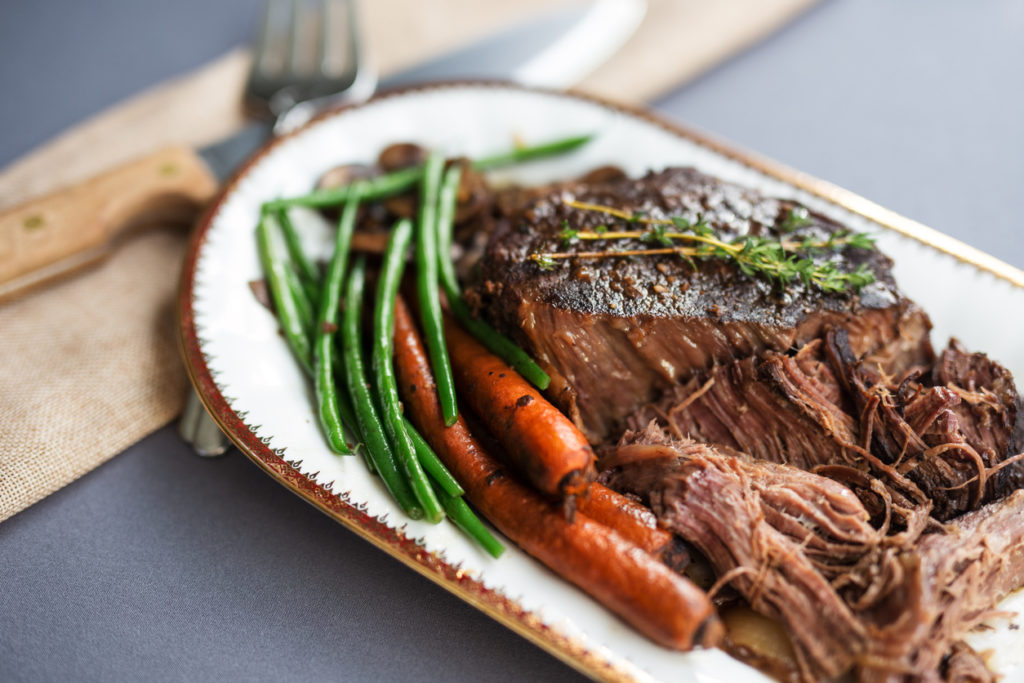 Slow cooked pot roast served with organic carrots, fresh green beans and sliced white mushrooms. Thyme garnish.