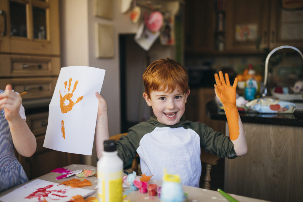 Little boy holding up his orange paint covered hand and a hand print painting.
