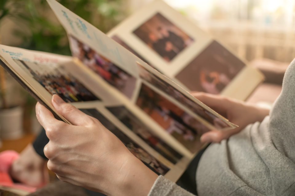 girl in a gray sweater is sitting on the sofa and looking at old photos in a photo album