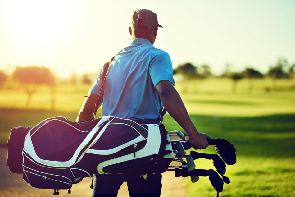 Man walking in between holes and holding golf bag