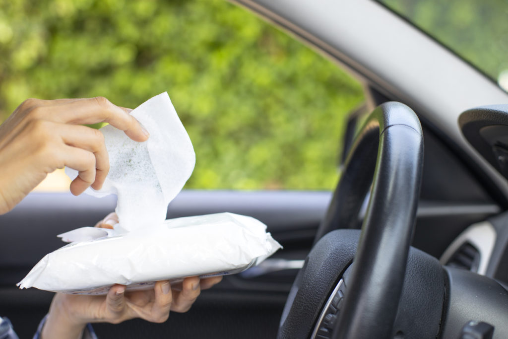 Woman's hand disinfecting the steering wheel of her car with sanitizing wipes