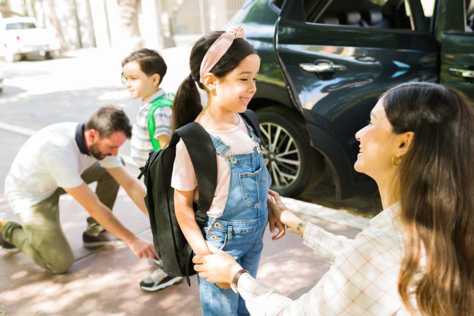 Pretty young girl smiling to her beautiful mom after getting out of the car to go to school with her little brother