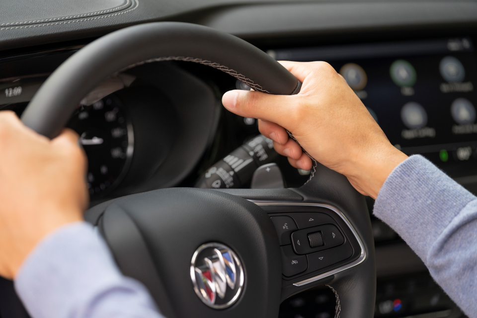 Hands on a the wheel of the Buick Envision. Technology in background.